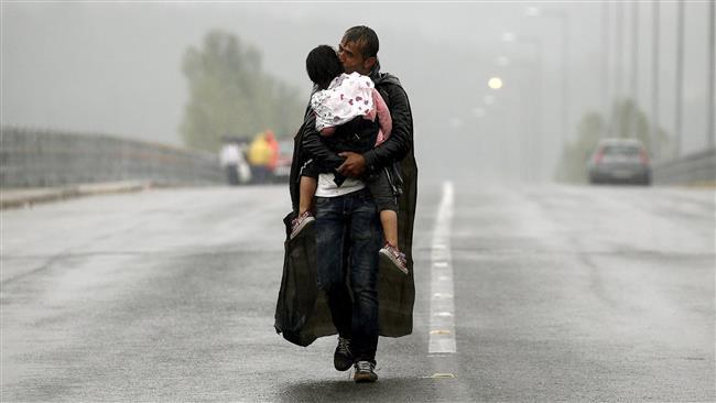 Yannis Behrakis: Refugiado sirio besando a su hijo.